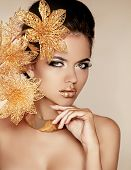 Beautiful Girl With Golden Flowers. Beauty Model Woman Face. Perfect Skin. Professional Make-up. Mak