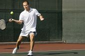 Male tennis player swinging tennis racket in forehand motion on tennis court