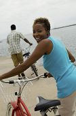 Portrait of a happy woman with bicycle and man in background on beach