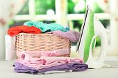 Steam iron and wicker basket with clothes, on bright background