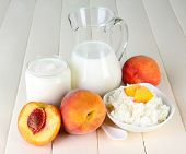 Fresh dairy products with peaches on wooden table close-up