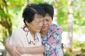 Candid shot of an Asian mature woman hugs and consoling her crying old mother at outdoor natural park.