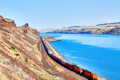 stock photo of chug  - Train chugging along Columbia River - JPG