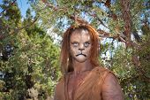 image of beast-man  - A Wild Lion man stares cautiously at the camera with a background of forest - JPG