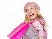 Sorridente menina adolescente no inverno chapéu e lenço com sacola de compras