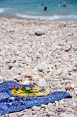 pic of costa blanca  - Sandals and towel situated at the pebble beach in Costa Blanca Spain with people playing in the Sea - JPG