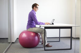 stock photo of stability  - man on stability ball working with tablet  - JPG