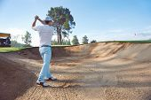 Golfer playing bunker shot