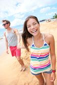 Beach people. Young  happy playful couple holding hands walking on beach having fun on travel vacati