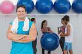 Portrait of a fit smiling young man with friends in background at fitness studio