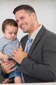 Happy businessman carrying baby boy while looking away at home