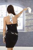 Back view of pretty woman in fancy mini dress, waving with hanky.