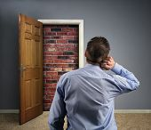 Brick wall blocking the office doorway for a businessman concept for conquering adversity, business