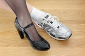 pic of stocking-foot  - Woman wearing one business shoe and sports shoe concept for work - JPG