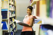 female african american college student leaning on book shelf in library