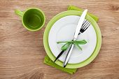 Fork with knife, blank plates, empty cup and napkin. On wooden table background
