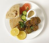 Homemade falafals (herbed and spicy chickpea balls) on a plate with Egyptian flat bread, lemon slice