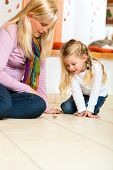picture of spinner  - Girl sitting with mother on floor playing with wooden toy spinner - JPG