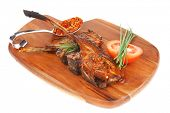 meat on wooden plate : roast ribs on wood with tomatoes chives and dry spices isolated on white back