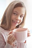 7 years old girl drinking hot cocoa from the big pink cup