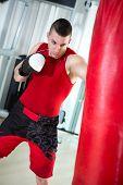 young muscular boxer punching bag