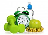 Green alarm clock, apple, bottle of water,  measuring tape and dumbbells as concept of diet - isolat