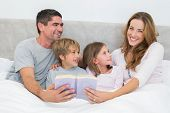 Portrait of happy woman holding storybook with family looking at her in bed