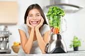 Green smoothie woman making vegetable smoothies with blender. Healthy eating lifestyle concept portrait of beautiful young woman preparing drink with spinach, carrots, celery etc at home in kitchen.