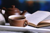 Cup of hot tea with teapot and book on table on bright background