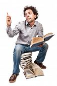 man reading and sit on pile of books