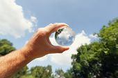 Holding a glass globe to blue sky,trees and field
