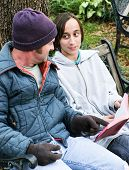 Homeless father and son reading the Bible, or a teen volunteer ministering to the poor.