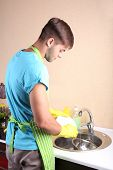 Man washing dish in kitchen