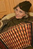 Elderly woman solder playing accordion