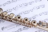 image of superimpose  - Silver flute superimposed on flute sheet music featuring a classical score - JPG