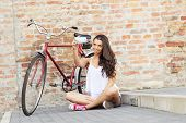 Beautiful woman with an old red bike-selfie photos of himself - in front of the brick wall