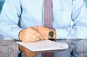 Businessman  Sitting At Office Desk And  Signing A Contract  By Pen