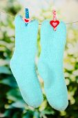 Colorful socks hanging on clothesline, on bright background