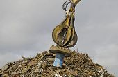 picture of junk-yard  - Large tracked excavator working a steel pile at a metal recycle yard with a magnet - JPG