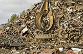 pic of junk-yard  - Large tracked excavator working a steel pile at a metal recycle yard with a magnet - JPG