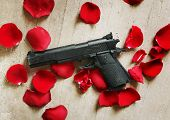Black gun red roses petals on the floor