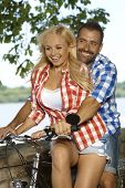 Happy casual smiling blonde woman getting a lift on bicycle by attractive man, outdoor.