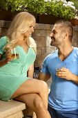 Romantic young couple dating outdoors with drinks in hand, looking at each other, smiling.