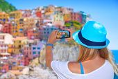 Back side of young woman taking picture of beautiful colorful old Italian buildings, happy travel to