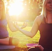 two women meditating in a yoga pose on the grass toned with a soft instagram like filter