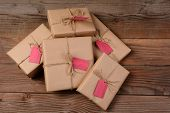 A pile of eco friendly wrapped Christmas Presents, on a rustic wood background.