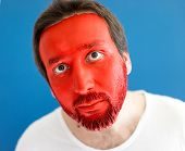 Man wearing shirt and painted red face
