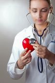 Doctor with stethoscope examining red heart, isolated on grey background