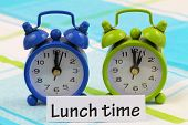 Lunch time card with two miniature clocks showing twelve and one o'clock