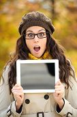 stock photo of jaw drop  - Surprised woman with glasses holding digital tablet blank screen in autumn - JPG